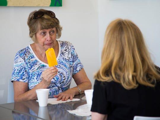 Cheryl Stillman (left) and Kim Rexing enjoy their popsicles