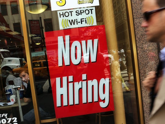 "A ""now hiring"" sign is viewed in the window of a business."
