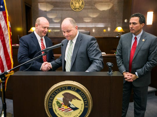 Assistant U.S. Attorney Geoffrey Brown, left, shakes