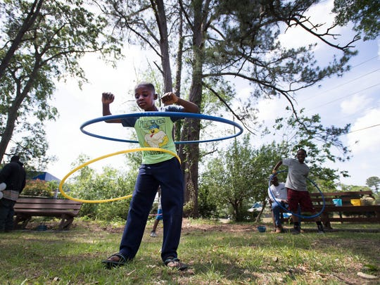 Donovan Mitchell, 9, hula hoops at an outdoor market on St. Helena Island on Saturday, April 15, 2017.