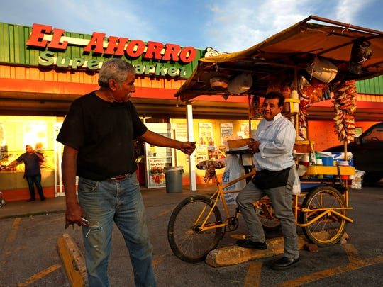 Isaac Morales, 52, right, of Mexico, sells snacks on March 23, 2017, in front of the El Ahorro Supermarket in Houston. Morales came to Houston more than 22 years ago from Guanajuato, Mexico.