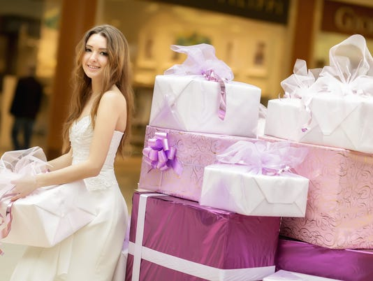 smiling girl in a white dress holds  box with gifts