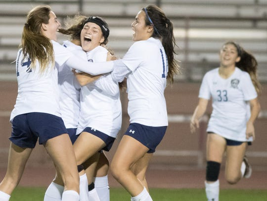 Jackie Calderon, center, celebrates with teammates