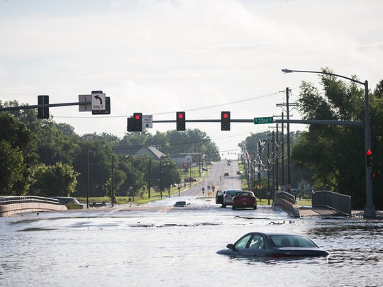 Two men sit stranded in their cars, surrounded by flood
