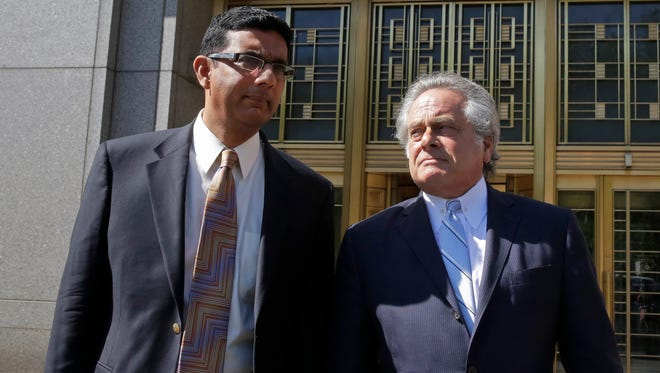 Conservative scholar and filmmaker Dinesh D'Souza, left, accompanied by his lawyer Benjamin Brafman leave federal court, in New York,  Tuesday, May 20, 2014.  D'Souza has pleaded guilty in New York federal court to making illegal campaign contributions. He admitted getting two close associates to make $10,000 contributions to Wendy Long. She was a candidate who lost the New York Senate race in 2012 to the Democratic incumbent. His plea agreement calls for a sentence of 10 to 16 months in prison. He'll be sentenced on Sept. 23.