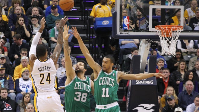 Pacers forward Paul George takes a shot against Celtics center Vitor Faverani and guard Courtney Lee at Bankers Life Fieldhouse.