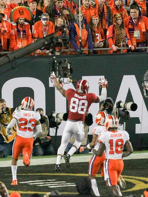Alabama tight end O.J. Howard (88) Mo scores on a 68-yard pass near Clemson safety Van Smith (23), left, and safety Jadar Johnson (18) during the third quarter of the National Championship game on Jan. 8 at Raymond James Stadium in Tampa, Florida.