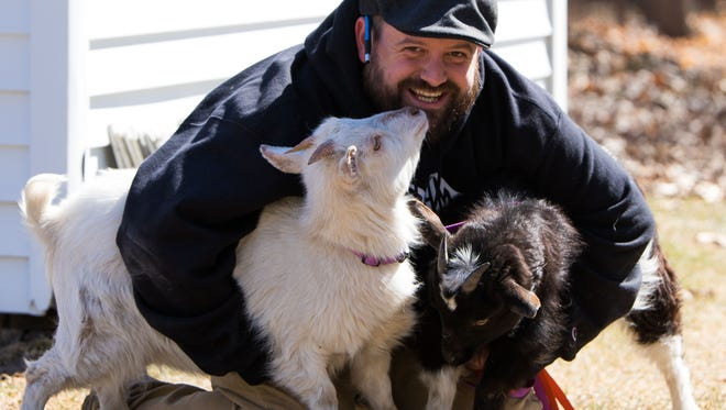 Jeremy Andrews, Executive Director at Sprout Urban Farms, with his goats George, right, and Wheezy.