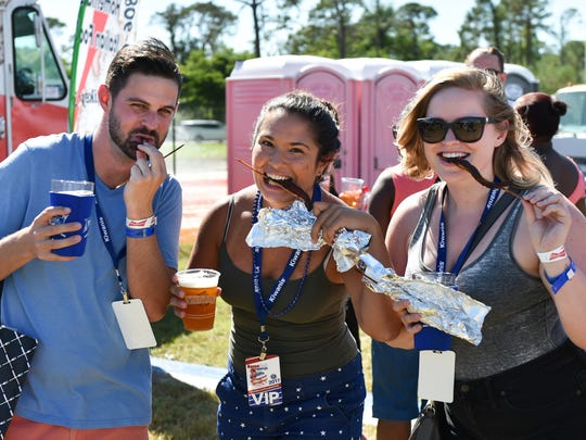 Brad Milici, Erika Macy and Paige Redmon devour their bacon on a stick during BaconFest.