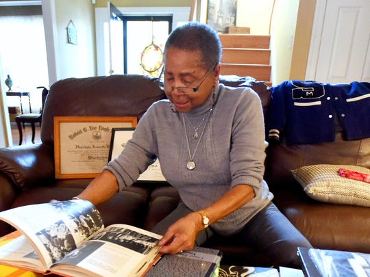 Rita Wilson looks through old Robert E. Lee High School yearbooks and other items that belongs to her children and grandchildren during an interview at her home in Richmond on Saturday, Nov. 7, 2015.