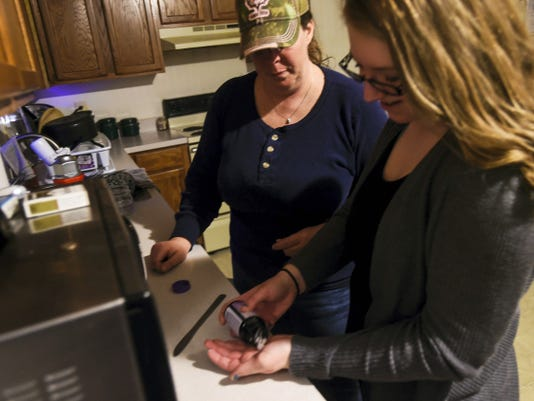 Kristin Reed, 15, takes a melatonin supplement before bed March 24 while her mother, Stacy Reed, helps at their home in Littlestown. Kristin's brain injuries have caused problems with sleeping and the melatonin helps her get needed rest at night before going to school in the morning.