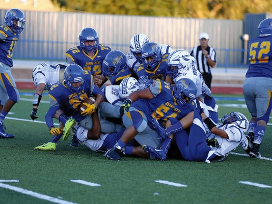 Bloomfield's Chauncey White, No. 22, gets taken down in a dog pile Friday during a game against Socorro at Bobcat Stadium in Bloomfield.