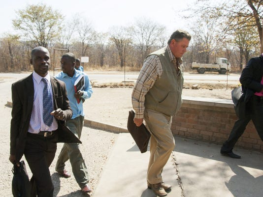 Theodro Bronkhorst, centre, a professional hunter, arrives for his appearance at the magistrates courts in Hwange about 700 kilometres south west of Harare, Wednesday, July 29, 2015. Bronkhorst who was granted 1000 bail has been charged with  failure to prevent an unlawful hunt that resulted in the killing of Cecil the lion by Minnesota dentist, Walter James Palmer, in Zimbabwe.  (AP Photo)
