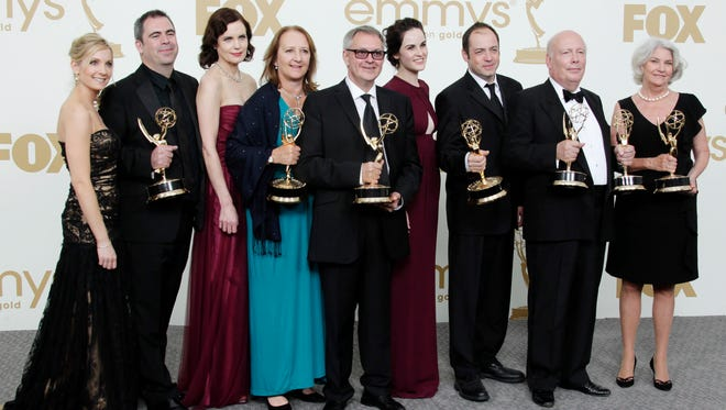 "In this Sept. 18, 2015 photo, ""Downton Abbey"" cast members, writers and producers pose with their first Emmys for outstanding writing and outstanding miniseries or movie at the 63rd Primetime Emmy Awards."
