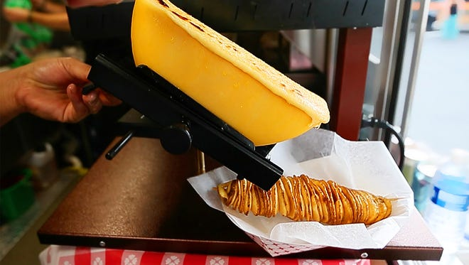 Moriah Tuck of Sweet Cheesus scrapes gouda cheese during a food truck event Jan. 27 at Millennial Brewing in downtown Fort Myers.