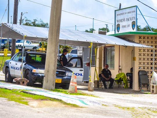Three Guam Police Department officers keep watch outside