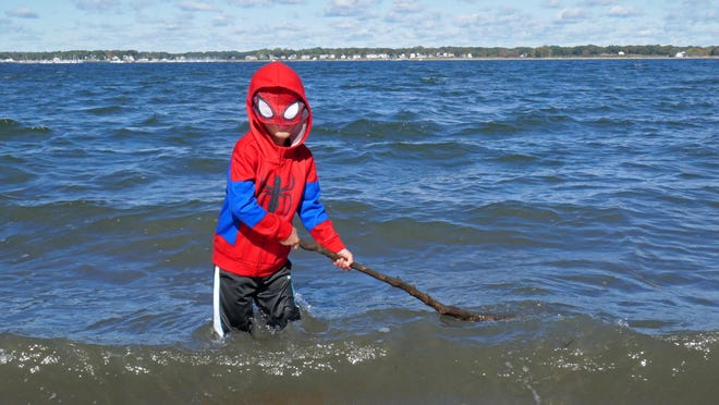Daniel McCormick, 6, of East Greenwich, doesn't let the autumn chill keep him out of the water on Saturday during a visit to Goddard State Park in Warwick with his family. Clad in his Spider-Man suit, he wades in up to his knees, splashing the water with a stick.
