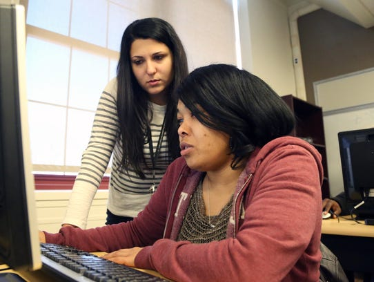 Dima Walters helps Elizabeth Abrams during GED classes