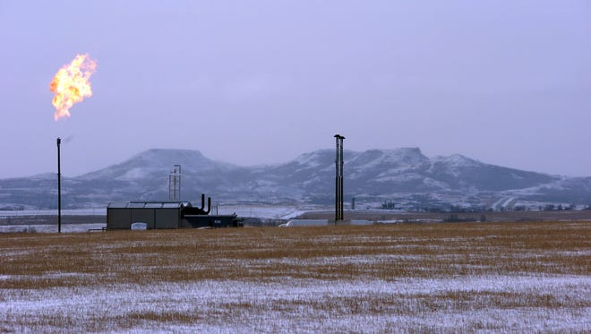 In this Feb. 25, 2015, file photo, a gas flare is seen at a natural gas processing facility near Williston, N.D. The Interior Department is moving to delay an Obama-era regulation aimed at restricting harmful methane emissions from oil and gas production on federal lands. (AP Photo/Matthew Brown)