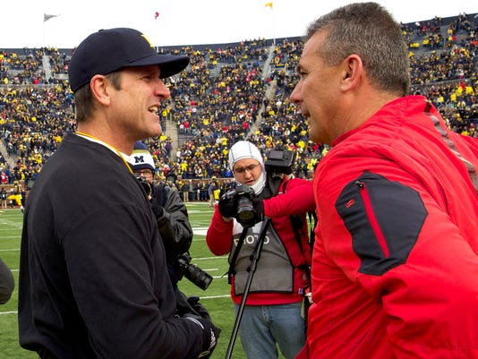 FILE - In this Nov. 28, 2015, file photo, Michigan head coach Jim Harbaugh, left, greets Ohio State head coach Urban Meyer on the Michigan Stadium field before an NCAA college football game in Ann Arbor, Mich. Harbaugh hopes to help Michigan upset Ohio State, a win that would put college football's winningest program in the Big Ten title game with a shot to win its first conference championship since 2004 and to earn a spot in the College Football Playoff. (AP Photo/Tony Ding, File)
