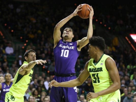 Kansas State forward Isaiah Maurice, center, pulls down a loose ball between Baylor guard Jake Lindsey, left, and forward Terry Maston, right, in the first half of an NCAA college basketball game, Saturday, Feb. 4, 2017, in Waco, Texas. (AP Photo/Rod Aydelotte)