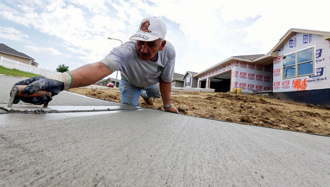 A construction worker shapes a sidewalk in front of new houses being built in Omaha, Neb.