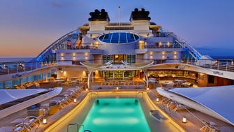 The main pool deck of the Seabourn Encore is a serene space with luxurious lounge chairs and a rectangular pool.
