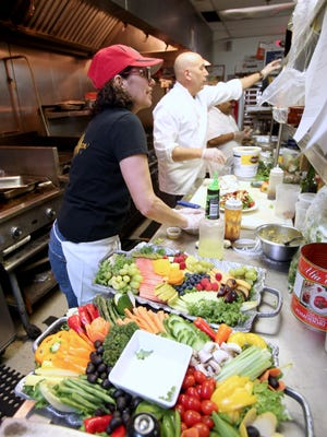 Andrea Grix and David Venitelli, chef and owner, work in the kitchen of Harvest Moon Caterers in Chestnut Ridge April 16, 2015.