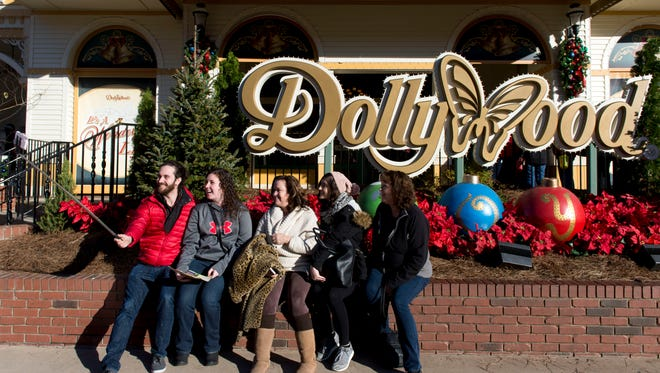 From left, Matt Karl, Sara Grant, Michele Karl, Tori Bonaventura, and Marlene Grant have photograph themselves in front of the Dollywood sign after the park reopened on Friday, December 2, 2016.