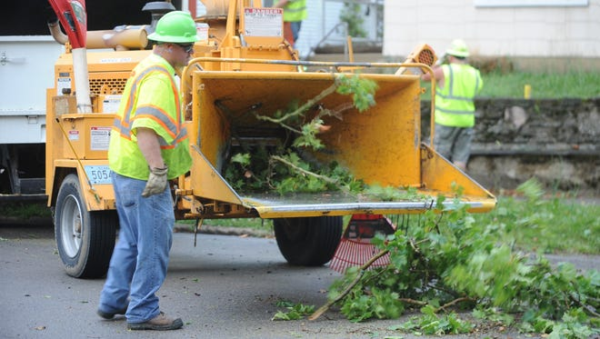 Richmond Street Department personnel work to clear a tree that fell onto the roof of a home in the 800 block of South Seventh Street during overnight storms in June 2016.