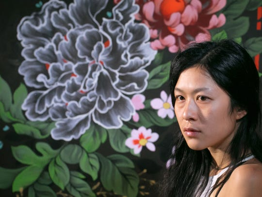 Detroit artist Ouizi poses for a photo by one of  her pieces for her solo show at Inner State Gallery on Thursday May 18, 2017 at her studio space in Detroit. Ouizi, whose know for her large scale murals of flowers, is the featured artist at this weekend's Flower Day at Eastern Market including having created the official poster.