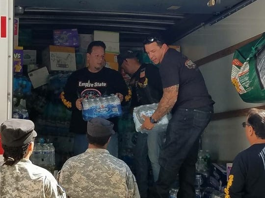 Members of the Latin American Motorcycle Association's Empire State chapter unloading supplies for the Puerto Rican hurricane relief efforts in Fishkill.