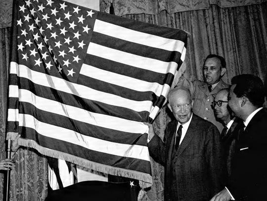 President Dwight Eisenhower helps unfurl the new 50-star