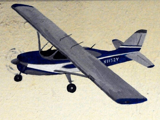 """A painting of the airplane Bob Terry flew under the blinking light in downtown Roby in 1968 adorns a wall in Roby's First Baptist Church Fellowship Hall. Terry used to own the building, the mural depicts this and other airplanes he used to own when he had a crop dusting business. His signature """"Bob Terry Yellow"""" was used on his planes in later years, after his pilot's license was reinstated."""