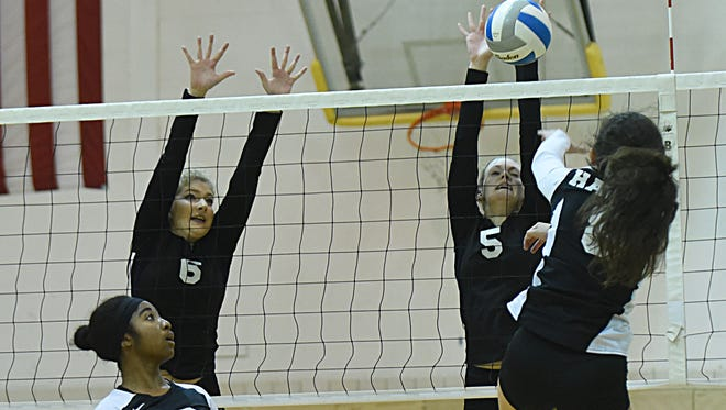 Farmington's Zoe Guthrie (6) and Jenny Cameron (5) try to block a spike by Harrison's Jenna Khoury in the city tournament.