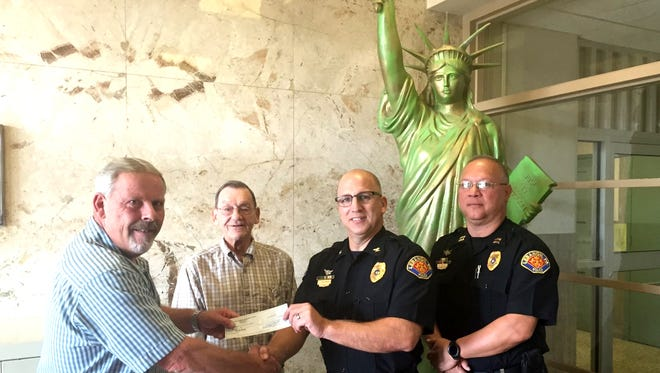 Scott Bergman, from left, manager of the Liberty Fire Co. Marching Club, and Liberty Fire Co. President Richard Bleistine, present a check for $10,000 to Lebanon police Chief Todd Breiner and Capt. David Gingrich. It's the third donation, totaling $20,000, that the club has given to city police in recent years.