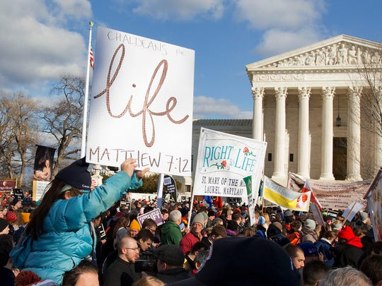 Anti-abortion demonstrators march past the Supreme