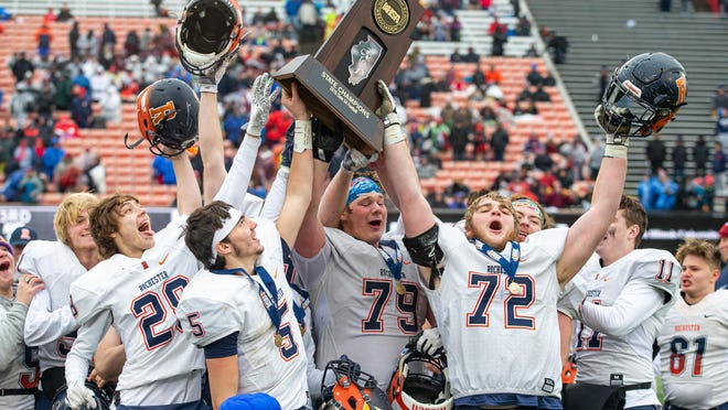 Rochester High School's Tanner Hayden (28), Clay Bruno (5), Chris Koerwitz (79) and Camden Ramsey (72) celebrate with the championship trophy after the Rockets defeated Chicago St. Rita 42-28 in the IHSA Class 5A state championship game at Huskie Stadium on the campus of Northern Illinois University, Saturday, Nov. 30, 2019, in DeKalb.