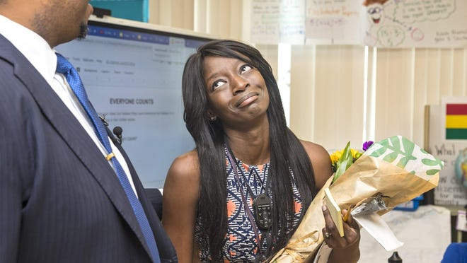 Syndie White, a third-grade math, science and social studies teacher at Elbridge Gale Elementary School in Wellington, is surprised by Schools Superintendent Donald Fennoy Thursday as he announces her as the school district's teacher of the year.