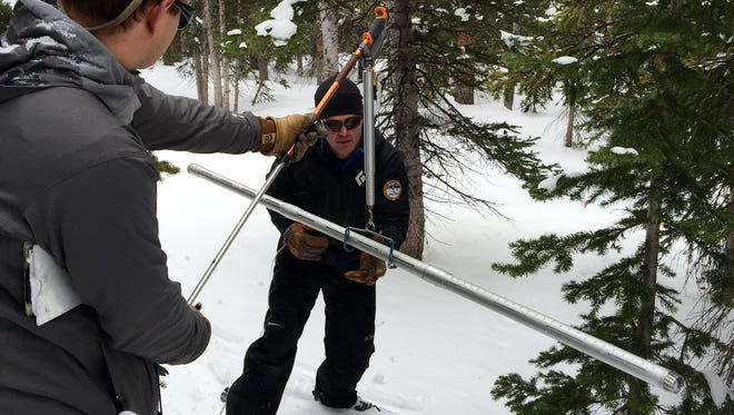 Hydrologist Brian Domonkos holds a scale used to weigh snowpack while technician Mike Ardison reads out the weight. Knowing how heavy the snowpack is helps scientists determine how much water it contains.