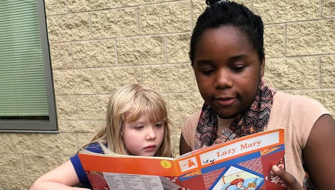 Hillside Elementary kindergartner Chloe Iliff listens to her sixth-grade reading buddy, Nina George.