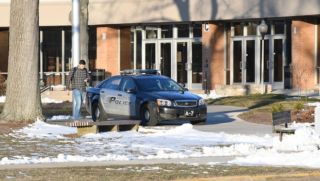A student walks by a police cruiser outside Ashland High School on Friday morning.