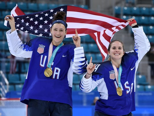 USA's Megan Keller, left, holds the U.S. flag with