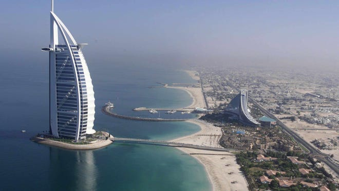 A 1999 file photo shows an aerial view of the ultra-luxurious 321-meter Burj al-Arab (l) or Arabian Tower, the world's largest hotel and the Jumeira Beach Hotel (r) on the Abu Dhabi highway.