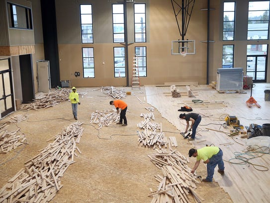 Workers install the hardwood floor at the the Marvin Williams Recreation Center.