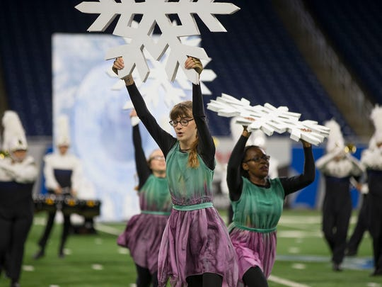 Color Guard members hold up snowflake props on the field during their performance.