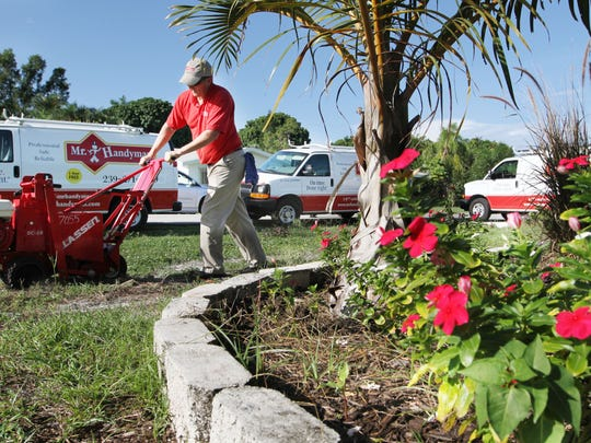 Don Gower, of Mr. Handyman, work to remove the old grass from the yard of veteran Doug Hale in preparation for new sod during a National Day of Service on Wednesday.