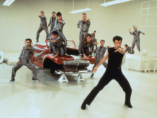 John Travolta leads a song-and-dance number about building