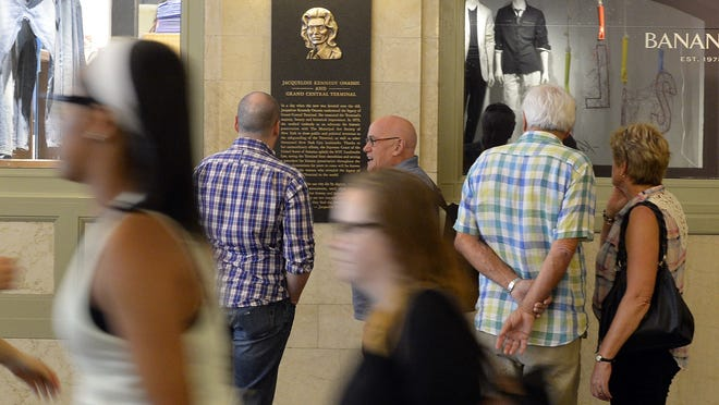 People walk past a plaque of Jacqueline Kennedy Onassis after a ceremony June 30, 2014 to dedicate Grand Central Terminal's renovated main entry vestibule in memory of first lady Jacqueline Kennedy Onassis, a former president of The Municipal Art Society of New York and former chairman of the city Landmarks Preservation Commission. Her efforts led to the U.S. Supreme Court upholding the city's Landmark Law in 1978 and saving Grand Central from having a 53-story tower built atop it. AFP PHOTO / Timothy A. CLARYTIMOTHY A. CLARY/AFP/Getty Images