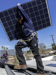 Alejandro DeLeon carries a solar panel as workers from